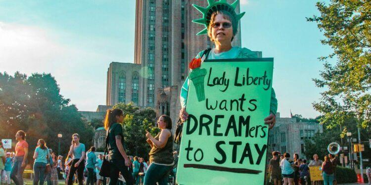 "Mujer sosteniendo un cartel que dice ""Lady Liberty wants dreamers to stay"" - DACA"