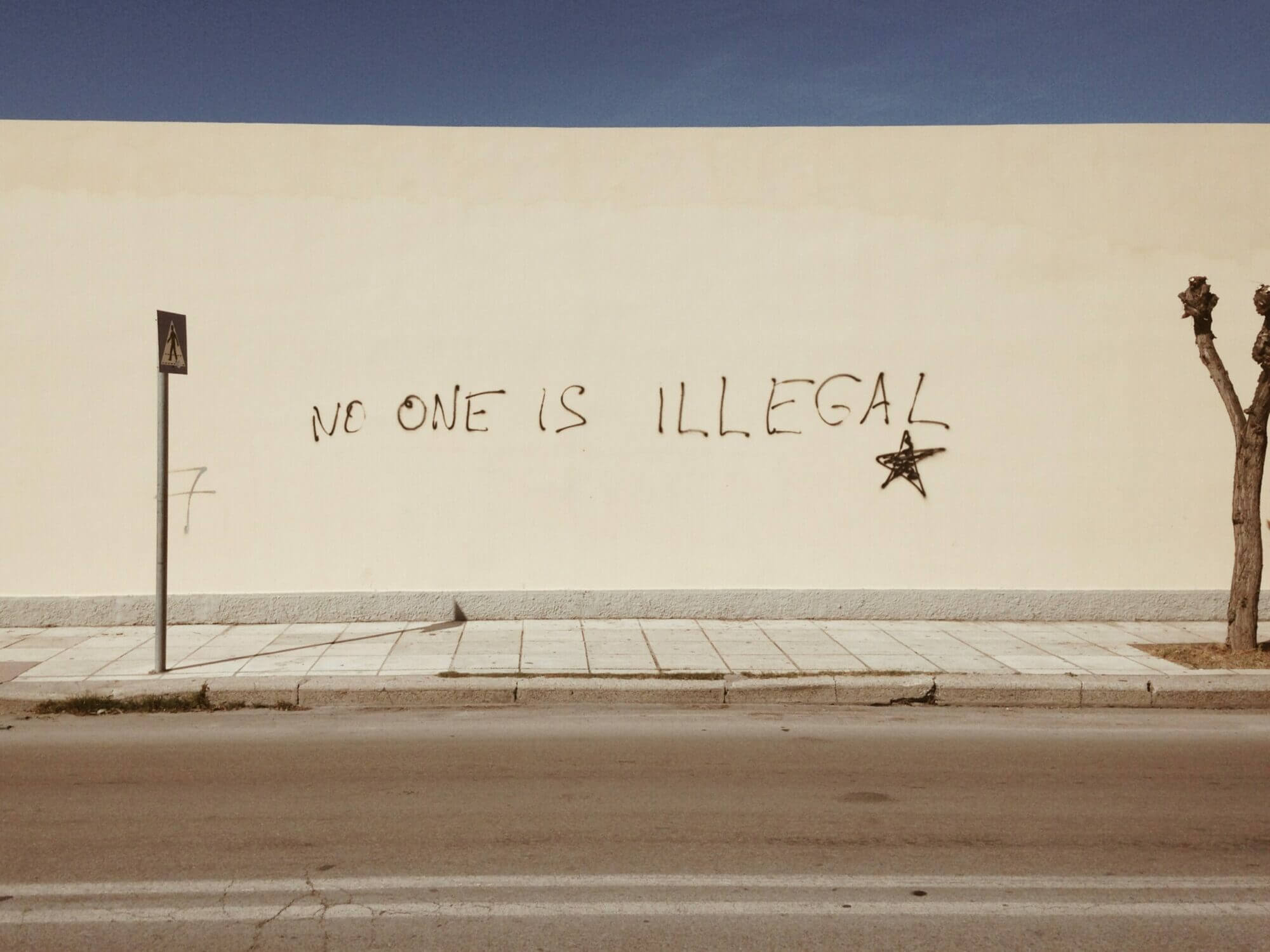 """Grafitti que dice """"nadie es ilegal"""" en inglés. En contra del bloqueo de la orden de deportación del bloqueo del juez federal deTexas"""