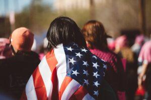 mujer con bandera de estados unidos en su espalda - este artículo habla acerca de los peligros que corre el programa DACA y los dreamers
