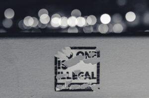 """Sticker que dice """"nadie es ilegal"""" este articulo trata acerca de las reformas en detenciones de ICE"""