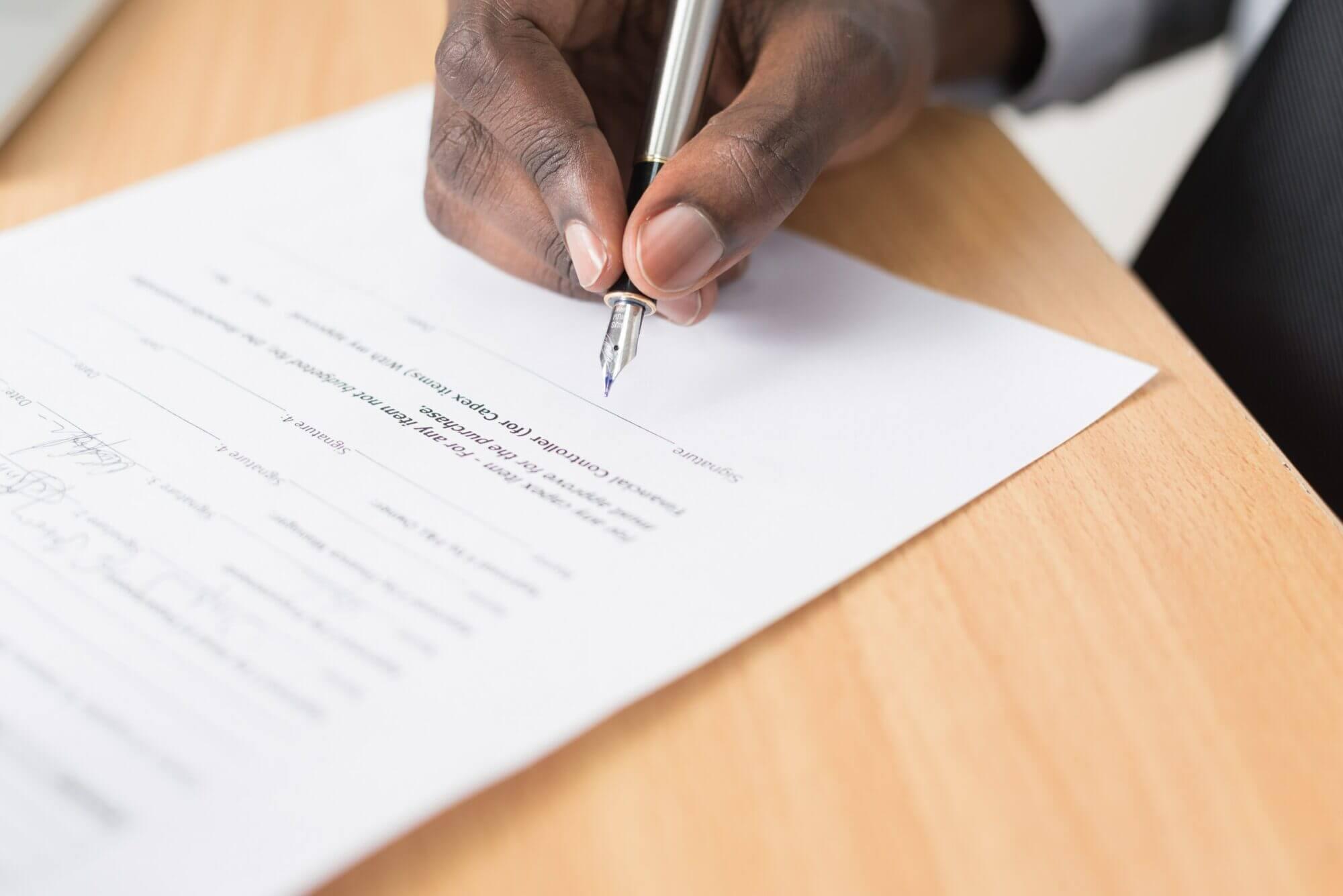 Persona firmando un papel - La normativa de la era Trump aceleraba los procesos y permitía realizar la deportación rápida.